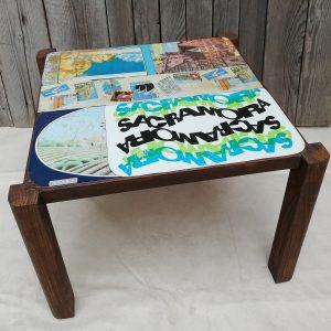 tavolino in legno massello con il piano rivestito di latte d'epoca tutte colorate
